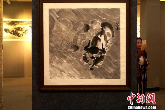 目前,孟繁华的绘画作品在西藏自治区群艺馆内展出。图为参加展览的观众浏览他创作的水墨写意牦牛画作品。 江飞波 摄
