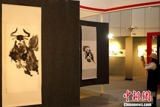 6月19日,一位观众在拉萨参观孟繁华水墨大写意牦牛个人画展,用手机拍摄绘画作品。 江飞波 摄