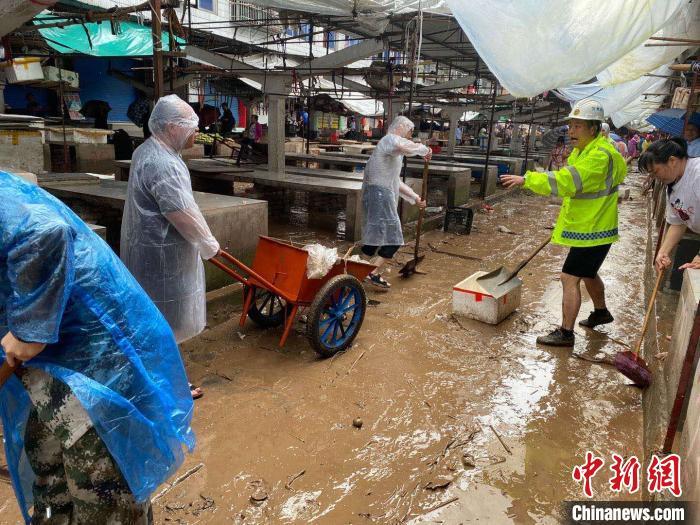 图为7月26日,暴雨引发的洪水过境后,重庆万州区分水镇政府干部职工及志愿者清扫淤泥和垃圾。  重庆万州区委宣传部供图 摄