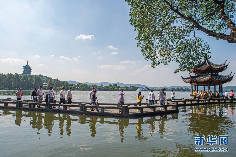▲游客在杭州西湖长桥景区游览(10月1日摄)。新华社发(江汉摄)